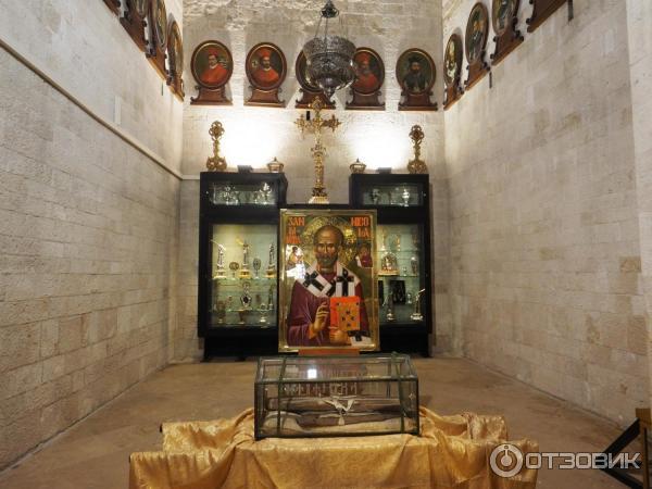 Икона св. Николая и сзади дары, многие из золота и серебра.